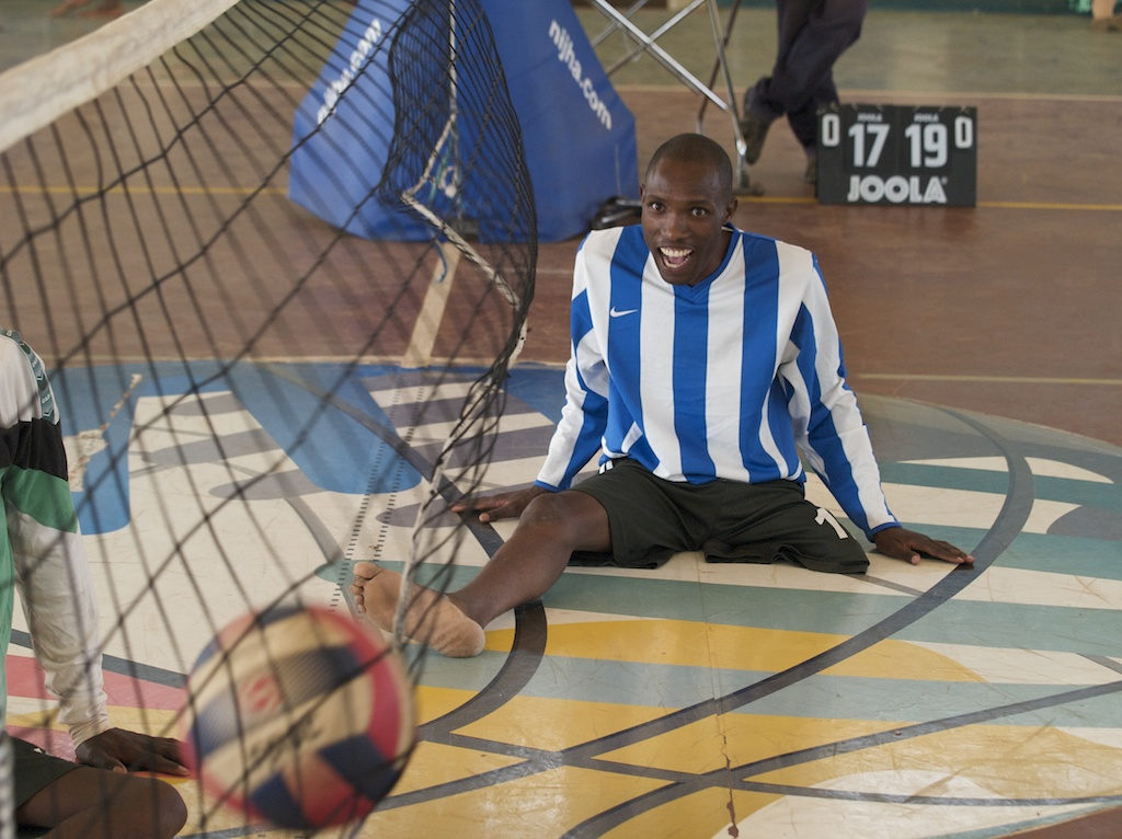 A man with one leg playing sit volleyball. He is smiling as the ball hits the net on the oppositions side