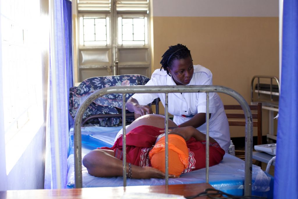 Midwife scanning a pregnant mum