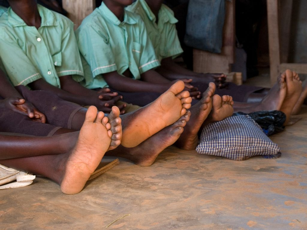 School children sit on the floor in a classroom in Uganda