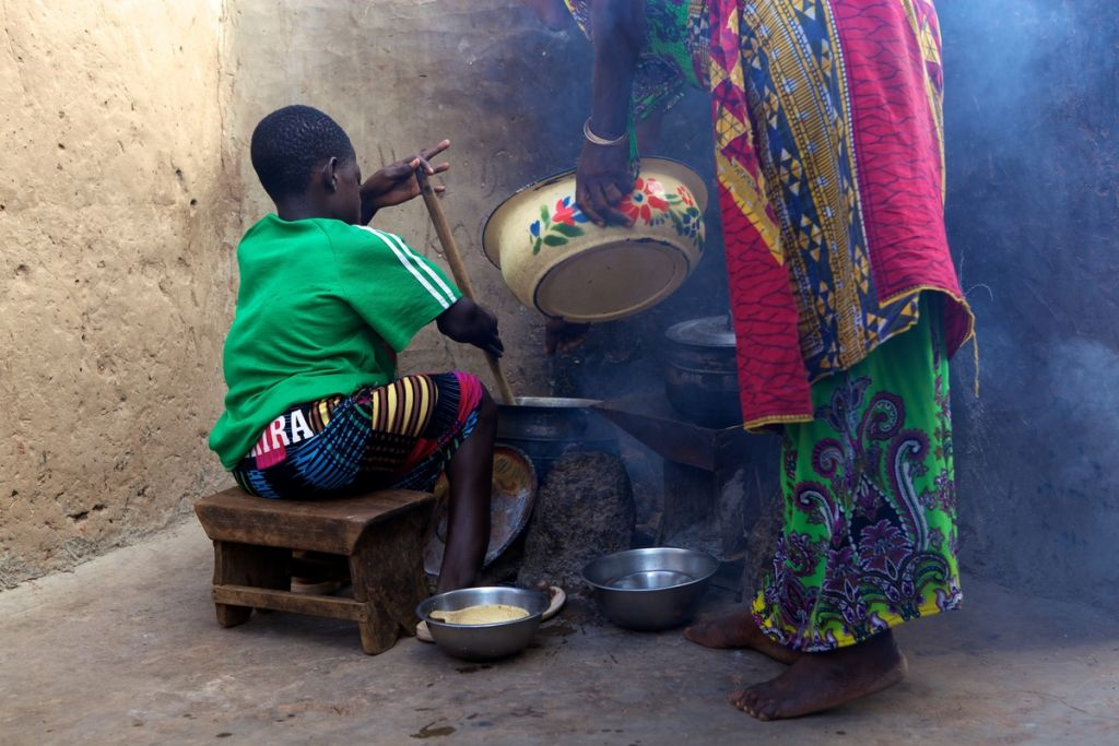 Girl helping her mother do the cooking, Ghana.