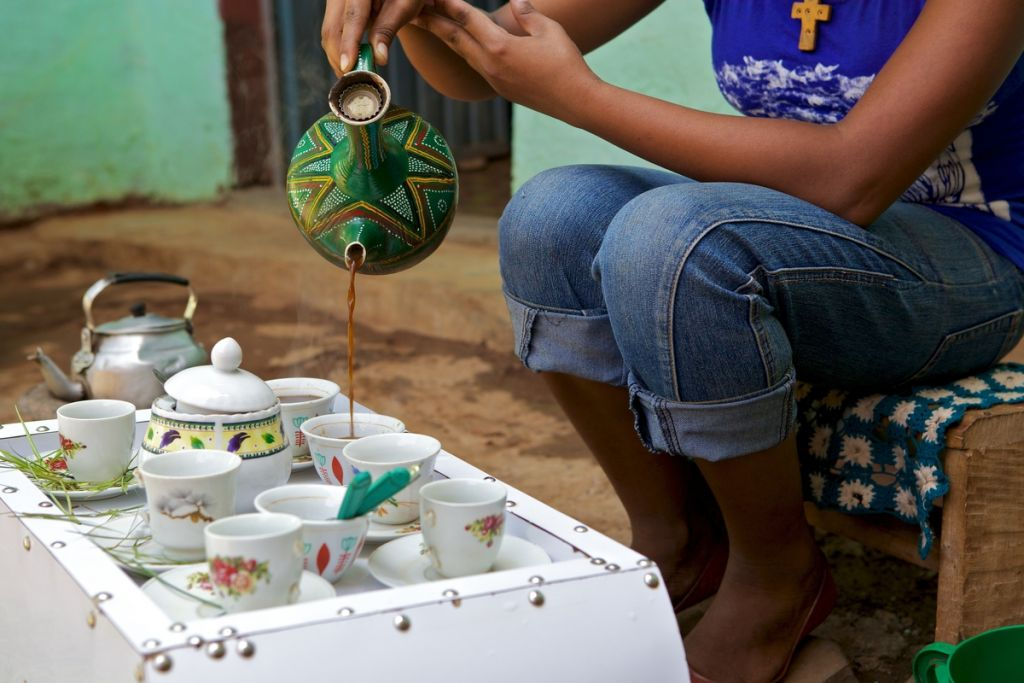 A traditional Ethiopian coffee pot pouring coffee at a coffee ceremony