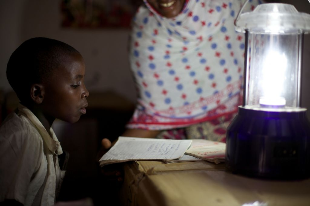Boy learning by solar power lantern