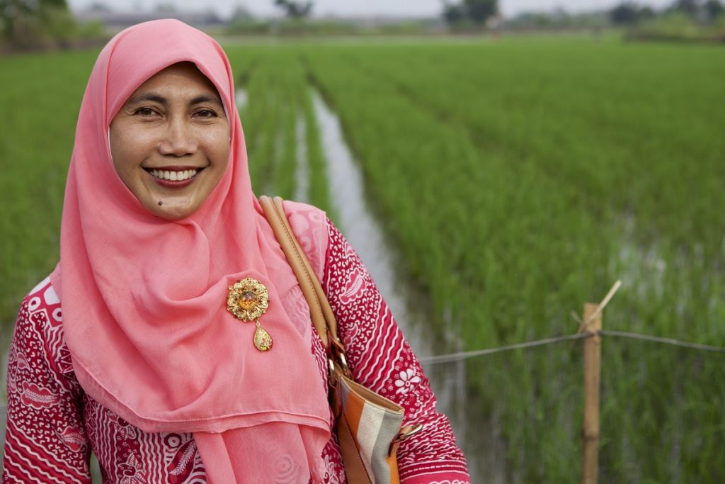 A lady wearing a pink headscarf smiling in front of a paddy field, Indonesia