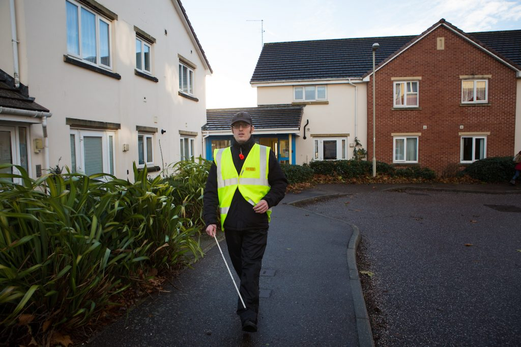 partially sighted man walking down the road using a white stick