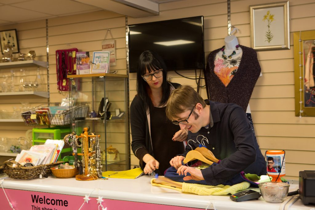 partially sighted man working at his local charity shop