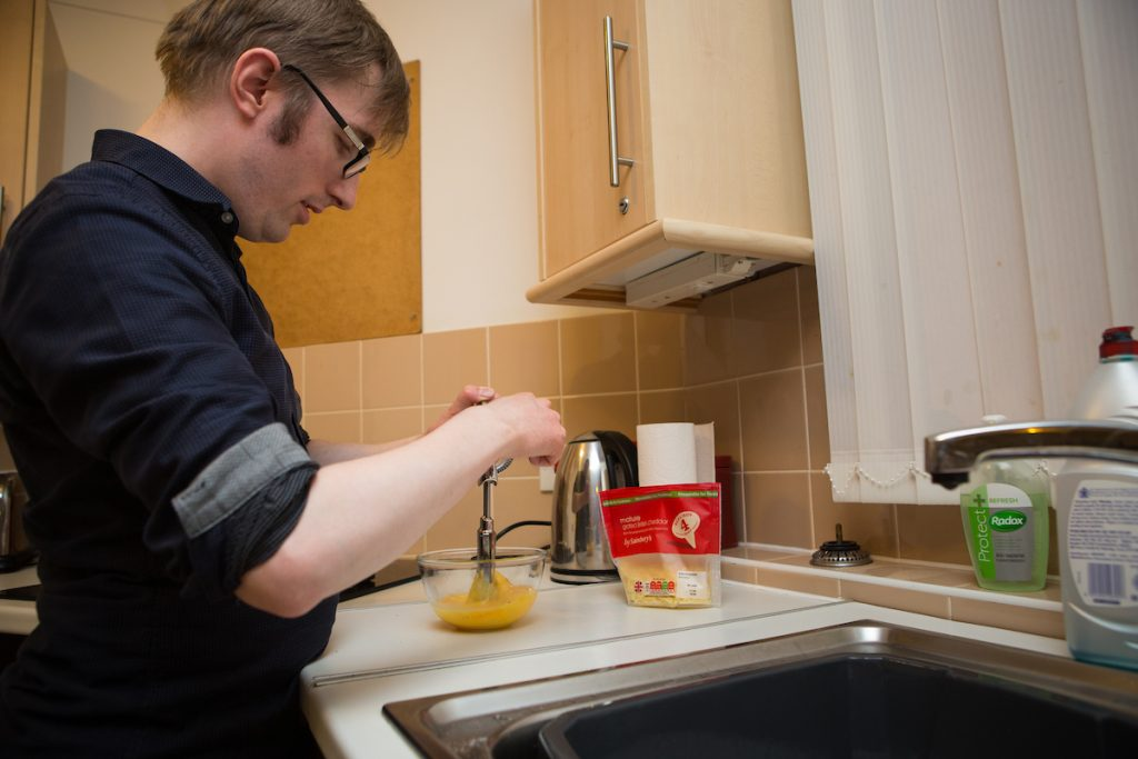 partially sighted man cooking in his kitchen