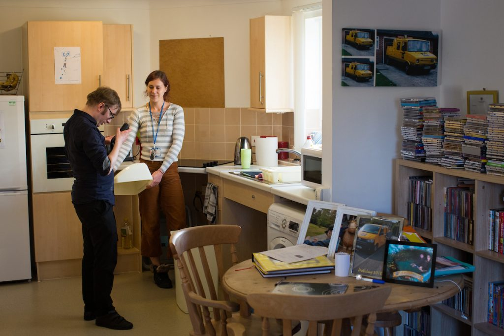 partially sighted man changing the bins in his kitchen alongside his keyworker