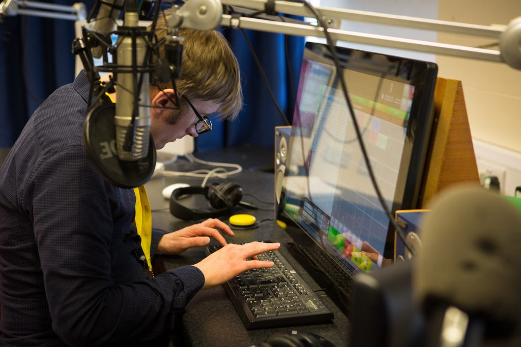 partially sighted man behind the mic of a radion station.