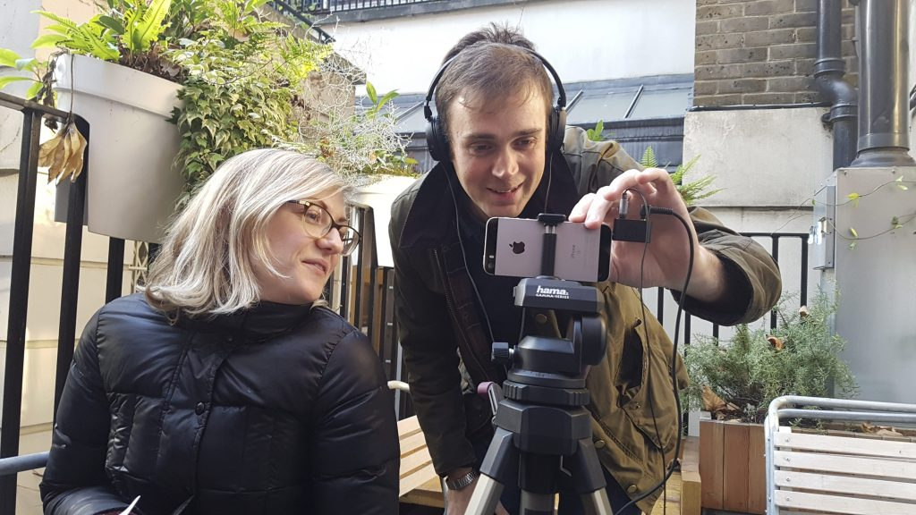 a man and woman using a smartphone on a tripod to conduct an interview