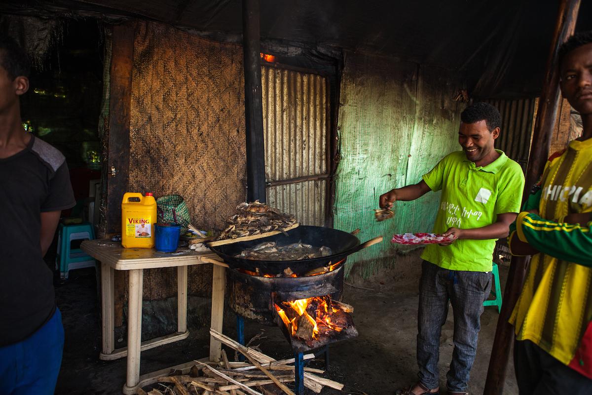 A fisherman frying fresh fish on a wood burning stove in Uganda.