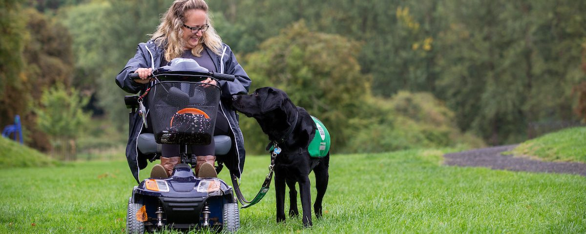 a woman sitting in a mobility scooter smiling at her black labrador assistance dog