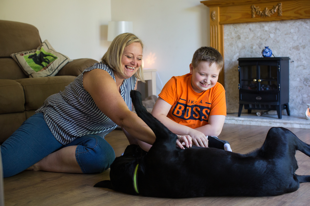 young boy and his mum with their Dogs for Good assistance dog